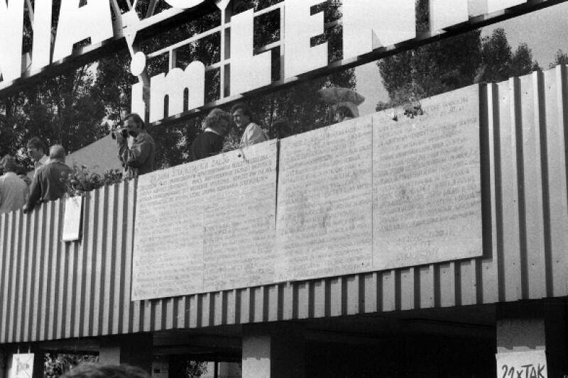 W poniedziałek, 18 sierpnia 1980 r., strajk wybuchł nowym płomieniem za sprawą 21 postulatów Międzyzakładowego Komitetu Strajkowego. Ich treść spisali na sklejkowych tablicach i wywiesili nad wejściem dla pracowników przy Bramie nr 2 Stoczni Gdańskiej dwaj młodzi działacze demokratycznej opozycji: Aram Rybicki i Maciej Grzywaczewski