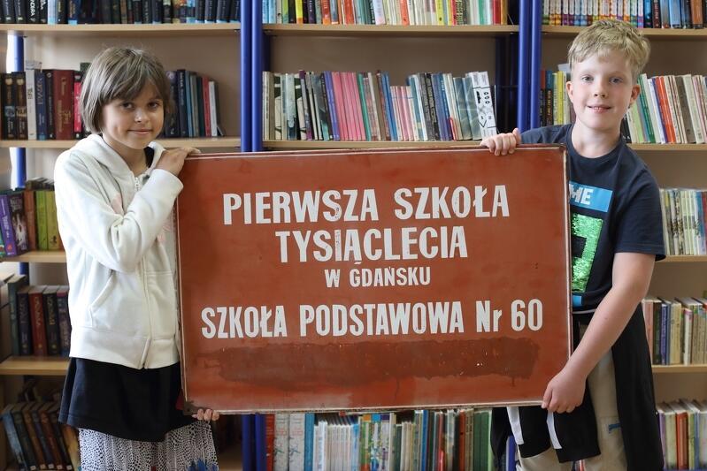 Maria i Damian, uczniowie Szkoły Podstawowej nr 60 trzymają tablicę wiszącą pierwotnie na budynku szkoły
