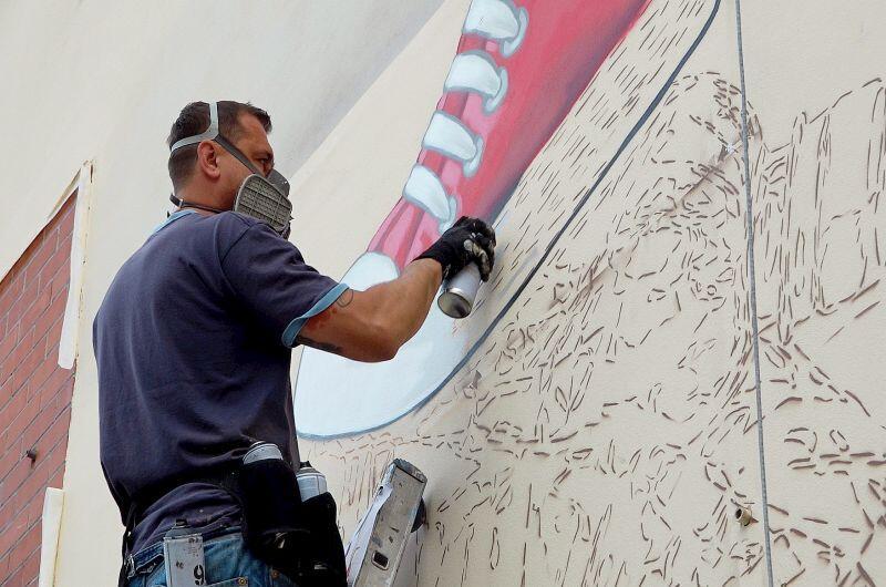 Marek Looney Rybowski w czasie prac nad muralem