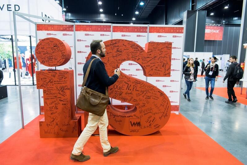 Hala wystawiennicza Amber Expo w Gdańsku podczas konferencji Infoshare. W tle widać stoiska targowe i kilka osób chodzących między nimi. Z przodu duże logo Infoshare w postaci liter IS i przechodzący przed nim mężczyzna w marynarce, w średnim wieku, z teczką na ramieniu