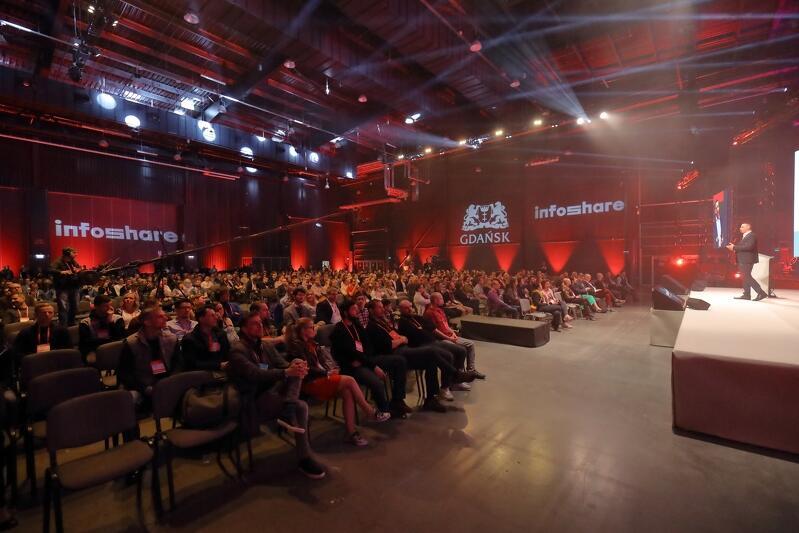 Otwarcie Infoshare 2019, scena Inspire, na scenie otwierający konferencję Grzegorz Borowski prezes zarządu Infoshare zwraca się do tłumu ludzi siedzącego na krzesłach w hali Amber Expo w Gdańsku, w której odbywa się otwarcie