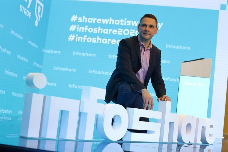 Grzegorz Borowski prezes zarządu Infoshare w studiu konferencji w Amber Expo, 24 września 2020, przyklęka na scenie za białymi literami układającymi się w napis infoshare. jest uśmiechnięty, ubrany w granatowy garnitur