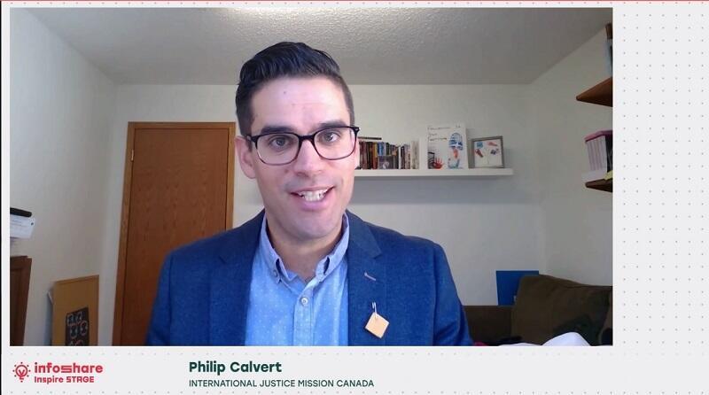 Philip Calvert z International Justice Mission Canada przemawia na scenie Inspire podczas Infoshare 2020 online, widać zrzut ekranu, na którym widać mężczyznę w okularach, młodego, w niebieskiej marynarce, ujęcie do pasa, przemawia z ekranu komputera prawdopodobnie w swoim domu, za nim widać drzwi wyjściowe z pokoju
