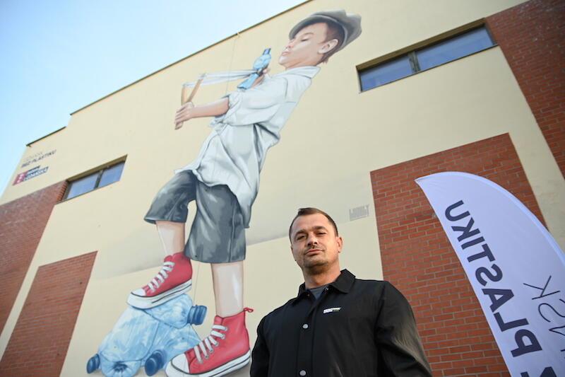 Nz. Marek Looney Rybowski ze swoim dziełem w tle, czyli pierwszym ekologicznym muralem, który powstał w ramach kampanii Gdańsk bez plastiku