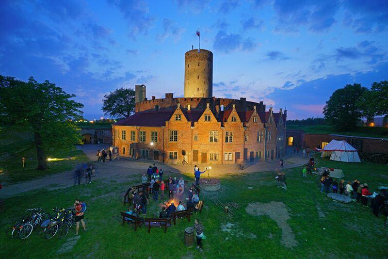 Nocne zdjęcie warowni z wieżą, otoczonej murem. Na pierwszym planie festyn historyczny