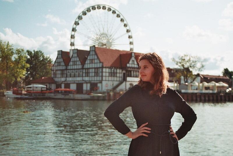 nastoletnia dziewczyna pozuje trzymając się pod boki, w tle widać rzekę Motławę w Gdańsku, a dalej koło widokowe