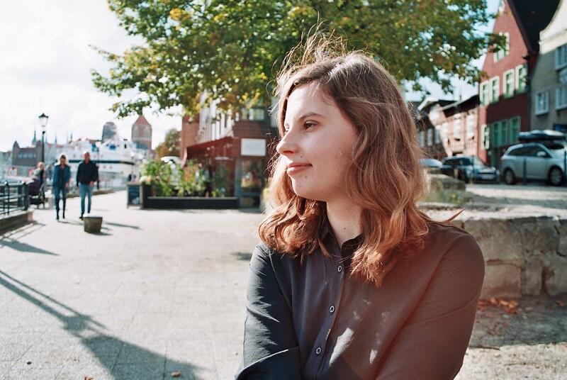 nastolatka o ciemnych długich włosach pozuje na nabrzeżu Motławy w Gdańsku, jest ubrana w czarną sukienkę