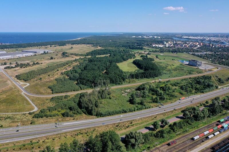 (z perspektywy drona) - ich granice na tym zdjęciu wyznacza ul. Sucharskiego (z przodu kadru, widać też przy niej tory kolejowe z pociągiem wiozącym kontentery), obszar centrum biurowego Koga (po prawej), z lewej zabudowa terminala DCT