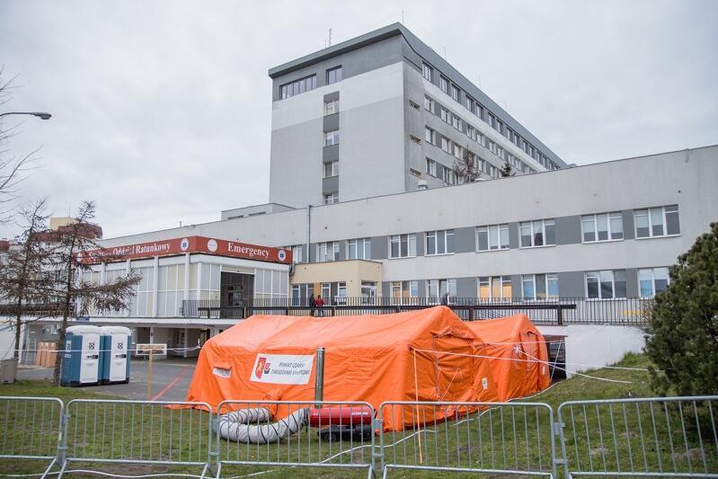 Budynek szpitala, przed nim dwa pomarańczowe namioty, obok dwie toalety toi toi