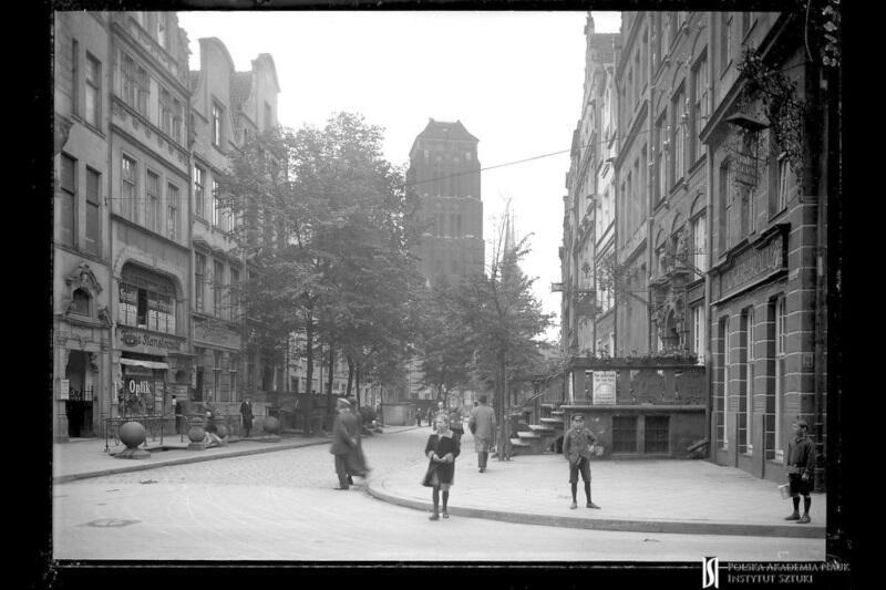 Archiwalna fotografia autorstwa Henryka Poddębskiego, prezentująca wieżę Bazyliki Mariackiej od ulicy Piwnej. Datowana jest na 1928 rok. Pochodzi ze zbiorów Centralnego Biura Inwentaryzacji Zabytków Sztuki