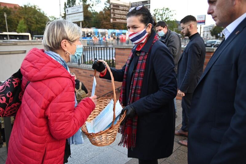 Prezydent Aleksandra Dulkiewicz rozdaje jednorazowe maseczki pod budynkiem LOT