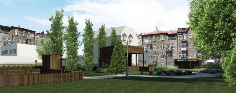 Na pierwszym planie w środku trawnik, na prawo fragment drzewa, po lewej płotek drewniany. Za nimi biały budynek z drewnianą altaną sceniczną osłonięty kilkoma drzewami. W tle wielopiętrowe budynki mieszkalne.