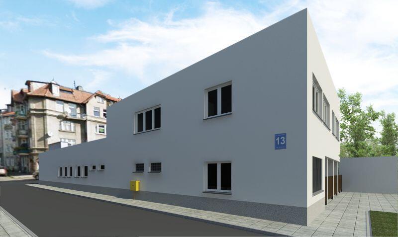 Na obrazku biały budynek (widoczne dwie ściany zewnętrzne) z kilkunastoma oknami. Na ścianie niebieska tablica z nazwą ulicy i numerem (Królikarnia 13). Przy budynku chodnik i asfaltowa droga. W tle po lewej fragment budynku mieszkalnego, po prawej drzewa.
