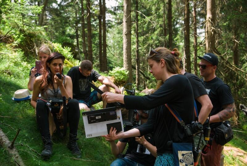 Kilka osób w lesie z kamerą i sprzętem, na pierwszym planie młoda kobieta z długimi ciemnymi włosami, ma apart fotograficzny przewieszony przez ramię, w ręku trzyma filmowy klaps