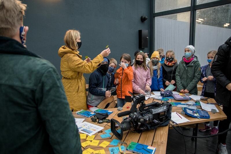 Na zdjęciu widzimy kobietę, blondynkę w maseczce na twarzy, i w długiej żółtej kurtce, która w rękach trzyma liście. Prezentuje je dzieciom w wieku wczesnoszkolnym
