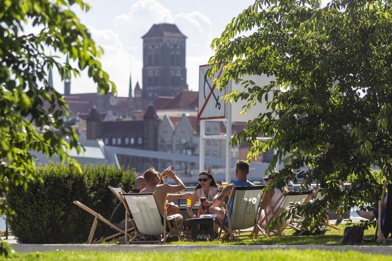 Panorama Gdańska od strony wyspy Ołowianka. Na pierwszym planie, pośród drzew, siedzi grupa osób na leżakach. W tle widoczne są zabudowania Głównego Miasta, z górującą wieżą Bazyliki Mariackiej