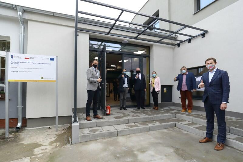 Z prawej Piotr Grzelak - zastępca prezydenta ds. zrównoważonego rozwoju - w towarzystwie społeczników działających na rzecz Nowego Portu i pracowników Klubu Aktywnego Mieszkańca. Stoją przed wejściem do wyremontowanego budynku