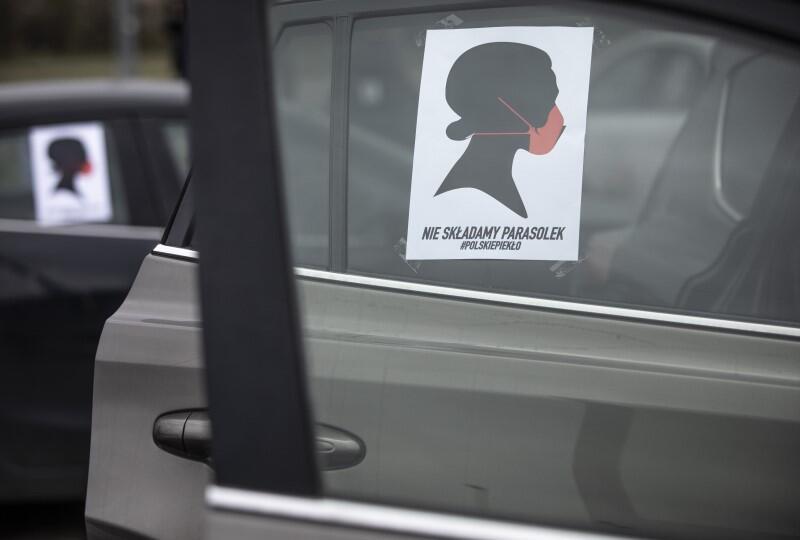 na szybie samochodu widnieje plakat - na rysunku jest czarny graficzny profil kobiety z czerwoną maseczką na ustach