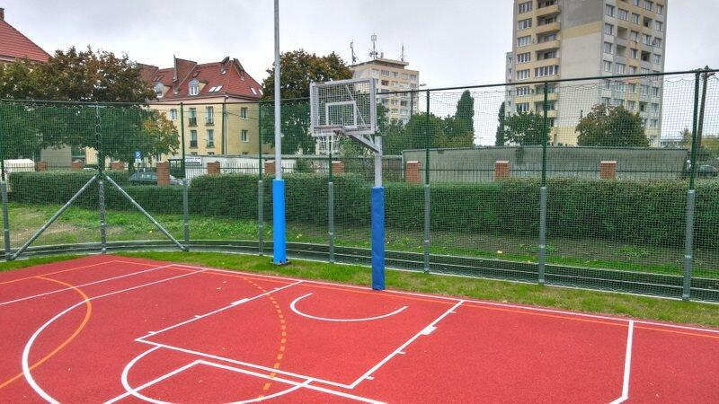 Boisko z koszem do gry w koszykówkę, w tle widać wieżowce.