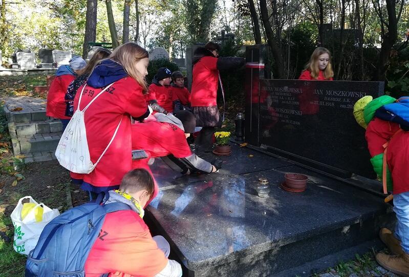 Wolontariusze ze Szkoły Podstawowej nr 59 w Gdańsku podczas akcji sprzątania grobów bohaterów, październik 2019, na zdjęciu - porządkowanie miejsca spoczynku Stefana Moszkowskiego, ułana, żołnierza Armii Krajowej, jeńca Stalagu 344 Lamsdorf