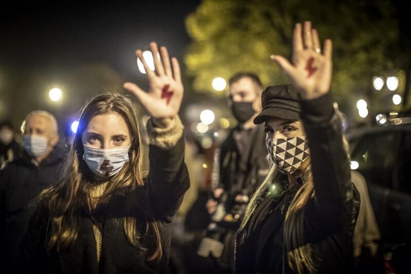 Dwie młode kobiety na Targu Drzewnym w Gdańsku. Jest wieczór, wokół trwa manifestacja. Kobiety demonstrują narysowany na wewnętrznej powierzchni dłoni znak protestu - czerwony piorun