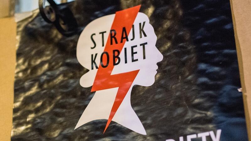 Znak Strajku Kobiet - czerwona błyskawica na tle zarysu kobiecej twarzy