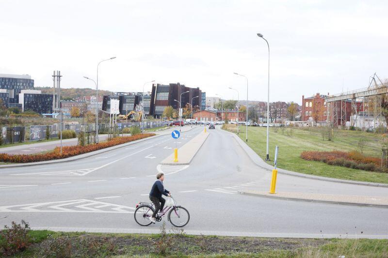 Ogólny plan ulicy, pustej o świcie. Jedzie rowerzystka i jedne samochód. Widać w oddali ECS, Pomnik Poległych Stoczniowców