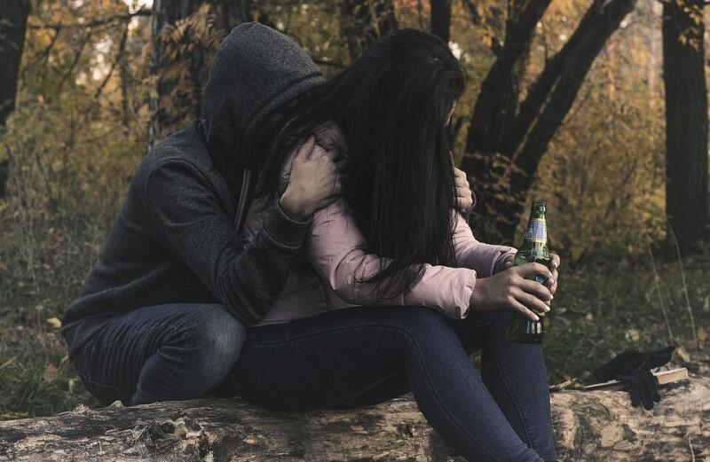 Dwie osoby z butelką alkoholu
