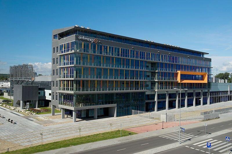 Budynek wielokondygnacyjny Amber Expo widziany z góry w słoneczny dzień, na pierwszym paleni ulica, po lewej parking