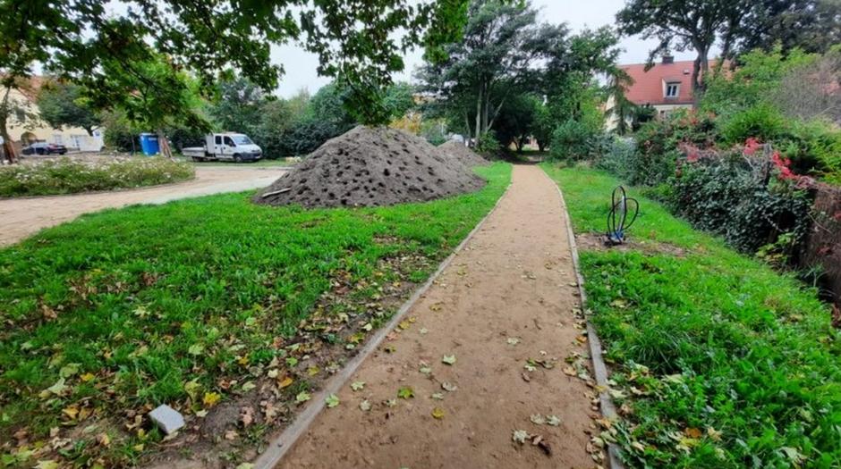 Na zdjęciu widać fragment ścieżki gruntowej, otoczonej zielonymi trawnikami. W oddali, po lewej stronie, stoi biały samochód, prawdopodobnie robotników