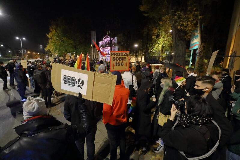 """Duża grupa osób z transparentami, stojąca przez ogrodzeniem i bramą wjazdową do siedziby Radia Gdańsk we Wrzeszczu. Zdjęcie zrobione z prawej strony grupy, manifestujący stoją twarzami do ogrodzenia. Na pierwszym planie, oprócz osób, widać dwa transparenty w formie tablic - na jednym jest symbol Strajku Kobiet - wizerunek profilu kobiety z wkomponowanym w ten profil symbolem błyskawicy oraz napis """"W imię matki, córki i umiłowanej siostry: wara od kobiet""""; na drugim - napis Proszę sobie iść, przy którym, z lewej i prawej strony, umieszczono symbol błyskawicy w kolorze czerwonym"""