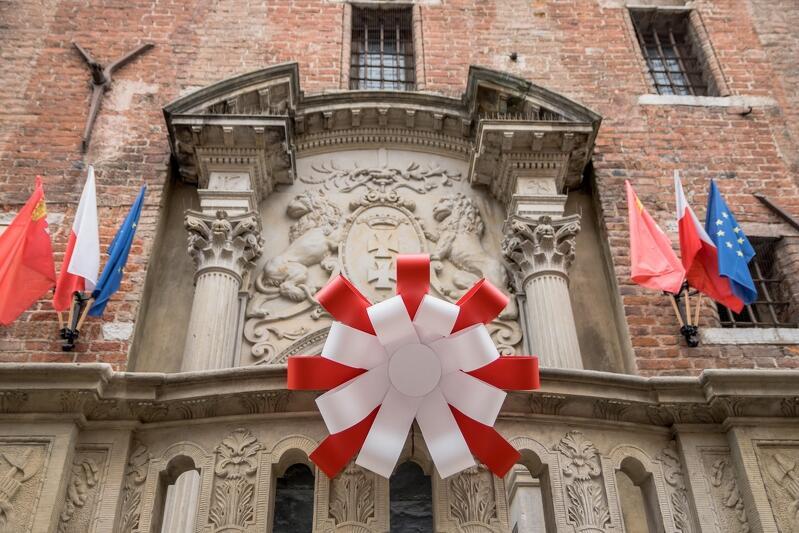 Biało - czerwona kokarda narodowa przed wejściem do Ratusza Głównomiejskiego