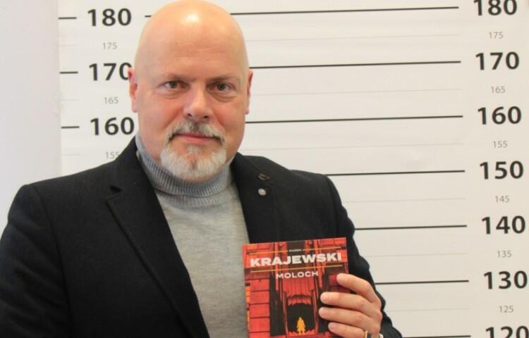 Mężczyzna, łysy z brodą, w marynarce, trzyma w ręku książkę