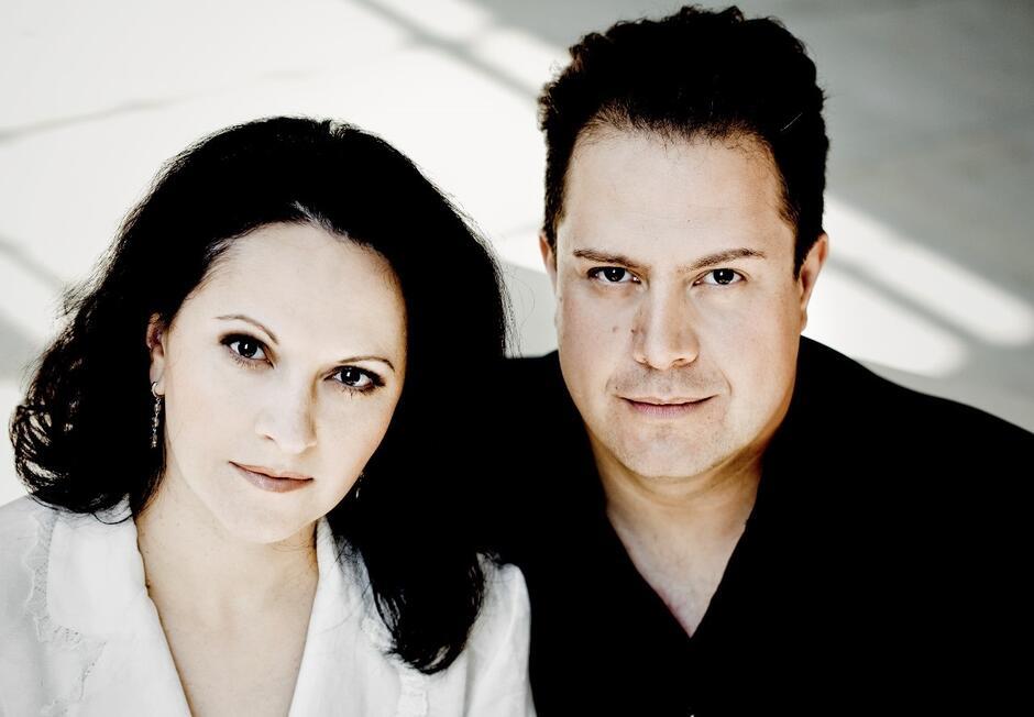 Zdjęcie portretowe przedstawiające parę bułgarskich muzyków, kobietę i mężczyznę. Kobieta, znajdująca się po stronie zdjęcia, ma białą koszulę z dekoltem, czarne włosy do ramion i delikatne srebrne kolczyki. Mężczyzna ubrany jest na czarno, również ma czarne włosy. Oboje patrzą w obiektyw. Zdjęcie jest prześwietlone.