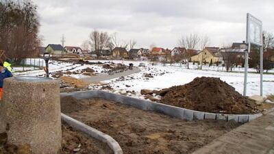 Plac ziemny, częściowo pokryty śniegiem. Na pierwszym planie betonowy śmietnik, w tle domy jednorodzinne, kilka bezlistnych krzewów
