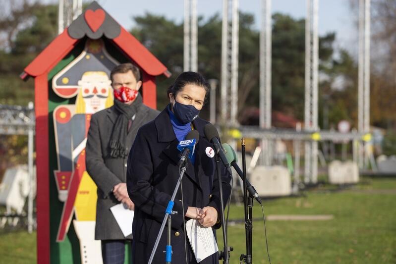 Kobieta w średnim wieku, w maseczce, stoi przy mikrofonie