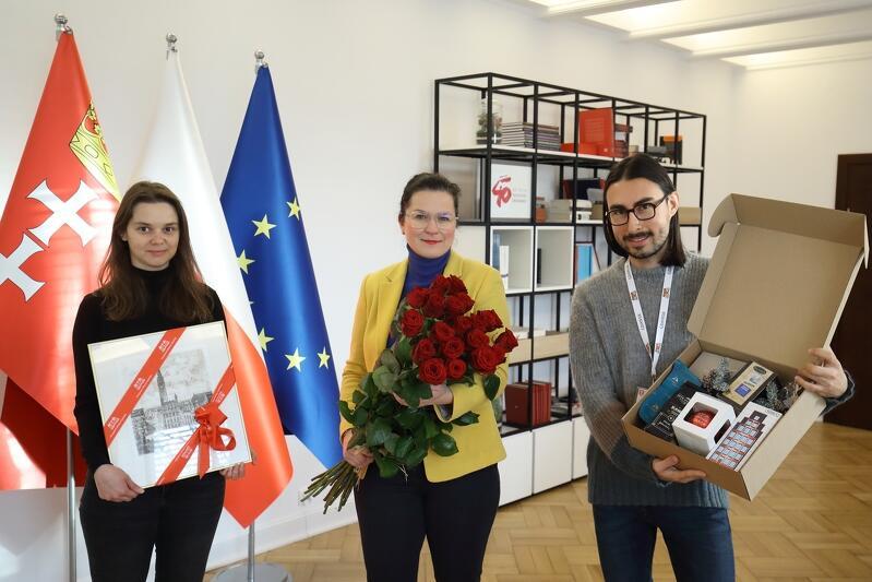 młoda kobieta ubrana na czarno, w rękach trzyma książkę, prezydent Aleksandra Dulkiewicz z bukietem kwiatów, młody mężczyzna z pudłem pełnym różnych podarków