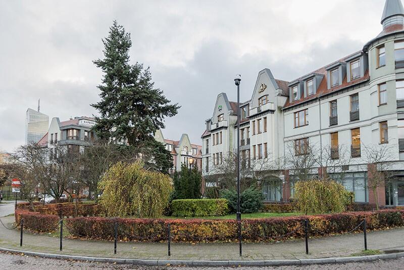 Zdjęcie przedstawia zadbany niewielki kolisty skwer, na którym znajdują się krzewy i kilka drzew. Skwer opasany jest niskim żywopłotem. Za skwerem znajduje się frontowa ściana czterokondygnacyjnego budynku mieszkalnego w kolorze białym