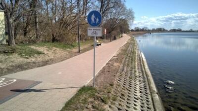 """Chodnik wzdłuż wody, brzeg zabezpieczony. Po lewej domy. Po prawej stronie chodnika stoki znak drogowy oznaczający """"droga dla pieszych"""""""