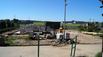 Na pierwszym planie chodnik i barierki, dalej rozkopana ziemia, na nich betonowe bloczki. W tle zielone pola