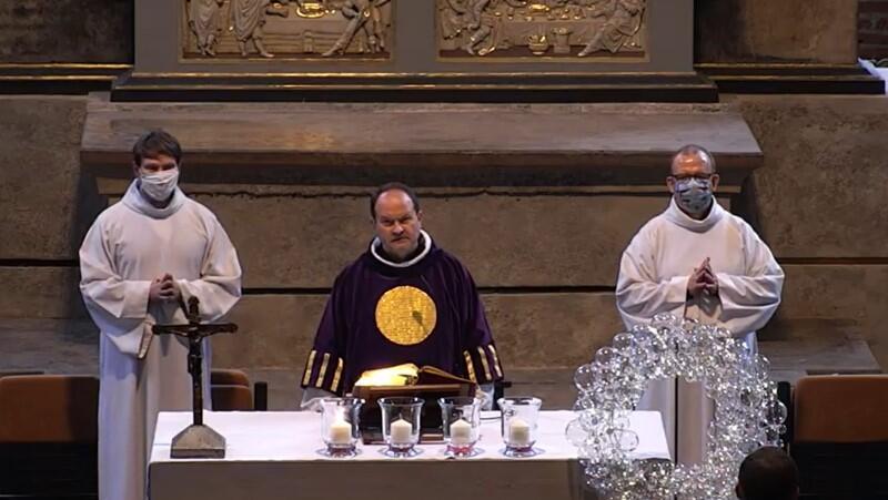 Wnętrze kościoła świętego Mikołaja w Gdańsku, widok na ołtarz. Za ołtarzem stoją trzy osoby. Pośrodku - ks. Krzysztof Niedałtowski w szacie liturgicznej koloru ciemnofioletowego, z dużym okręgiem koloru złotego na piersi. Na prawo i lewo od księdza stoją dwaj mężczyźni - ministranci w długich, białych szatach, tak zwanych albach