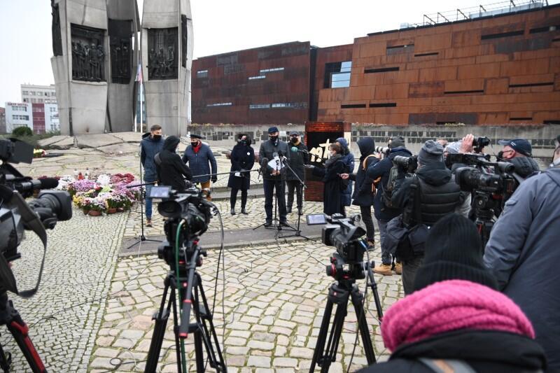 Pomnik, ludzie pod pomnikiem, kamery, mikrofony