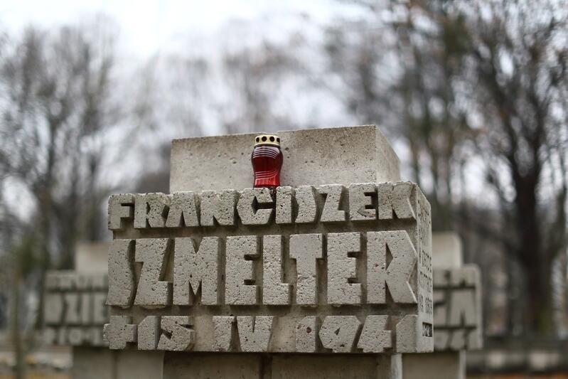 kamienny nagrobek z przestrzennymi literami pisanym imieniem i nazwiskiem oraz datą śmierci, na nagrobku stoi czerwony znicz