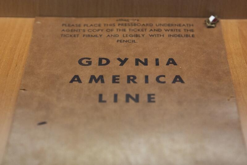 Zżółkła sztywna karta z napisem Gdynia America Line i napisami dla pasażera w języku angielskim