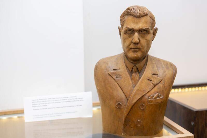 Popiersie z jasnego drewna, przedstawienie mężczyzny o krótkich włosach z przedziałkiem z boku, w marynarce i pod krawatem