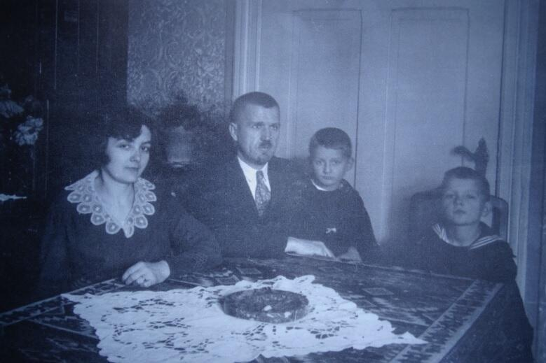 rodzina siedzi przy stole: matka, ojciec - na kolanach starszy syn, obok młodszy, czarno białe zdjęcie