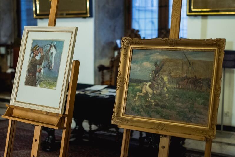 Dwa obrazy wyeksponowane na sztalugach, pierwszy pionowy ukazujący łeb konia i stojącego przy nim żołnierza, drugi poziomy - jeździec jadący na koniu przez łąkę
