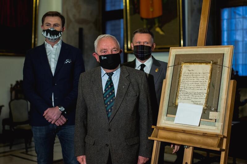 Trzech mężczyzn pozuje przy rewersie obrazu na sztalugach, wszyscy w maseczkach, stojący z przodu to starszy siwy pan, za nim młody wysoki oraz średniego wzrostu i wieku