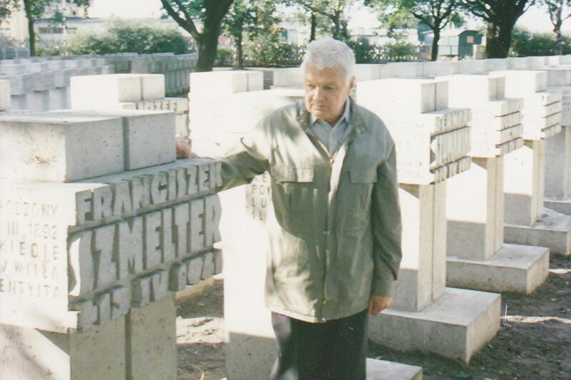 mężczyzna dotyka ręką kamiennego nagrobka i patrzy na niego