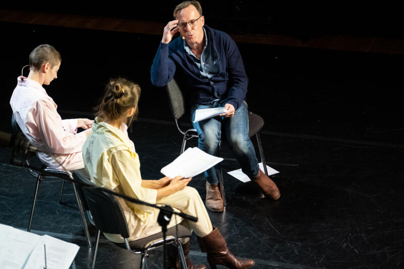 Zdjęcie z czytania performatywnego w klubie Żak. Na czarnej scenie, na czarnym tle siedzi troje aktorów - przodem do aparatu Arkadiusz Brykalski, mężczyzna w średnim wieku, opalony, w błękitniej koszuli, granatowym swetrze, dżinsach, brązowych butach, okularach. W lewej ręce trzyma kartki, prawą podpiera głowę. Po jego lewej bokiem do aparatu siedzi Magdalena Gorzelańczyk - kobieta pod 30-tkę, krótko ogolona, w jasnoróżowym kombinezonie, patrzy w kartkę. Obok niej, tyłem do aparatu Beata Niedziela, kobieta ma jasnożółty kombinezon i skórzane brązowe kozaki na obcasie, w rękach trzyma kartki, patrzy na mężczyznę.